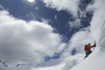 Mountain climber going up snowy slope with axes