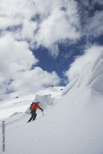 Hiker going up snowy mountain slope