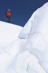 Mountain climber hiking past ice formation