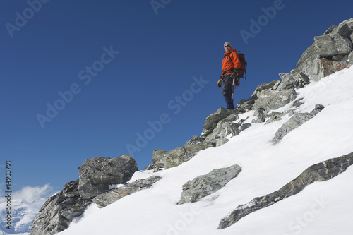 Mountain climber descending snow and boulder slope