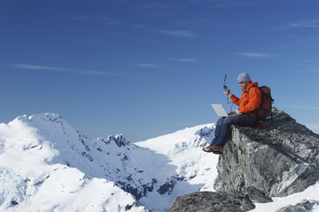Mountain climber using laptop with walkie-talkie on mountain peak