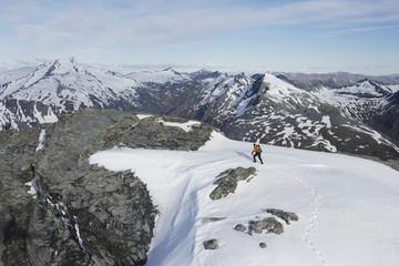 Mountain climber heading across snow for distant peak