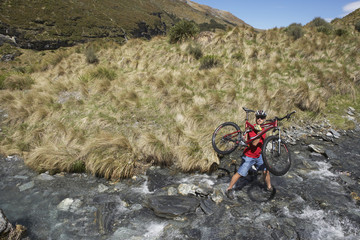 Cyclist carrying bike in river