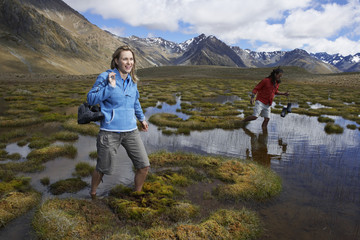 Two hikers wading through pond by mountains