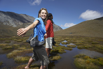 Two hikers holding hands wading through pond between hills