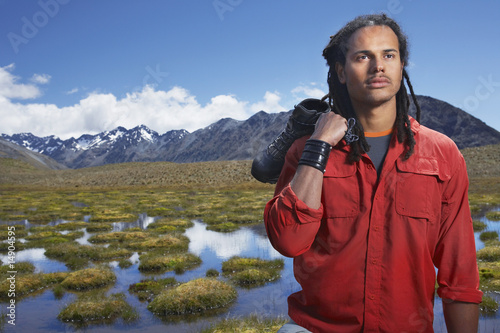 Man holding shoes by ponds near mountains
