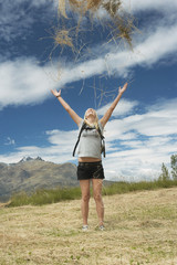 Female hiker throwing grass into air in field