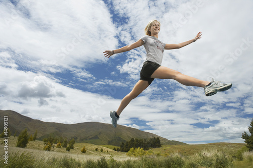 Woman leaping in hills