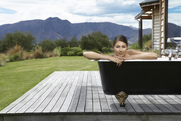Woman taking bath on porch near mountains