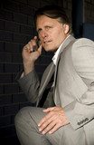 Nervous and anxious looking businessman on celphone. poster