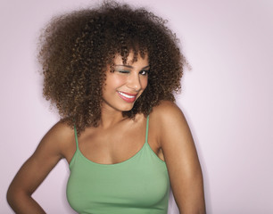 Woman with Curly Hair winking in studio, half-length