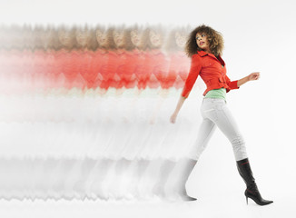 Woman with curly hair walking  in studio, multiple exposure
