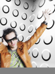 Man wearing headphones and sunglasses, blurred motion, in front of spotty wall