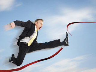 Business man jumping through red tape, digital composite
