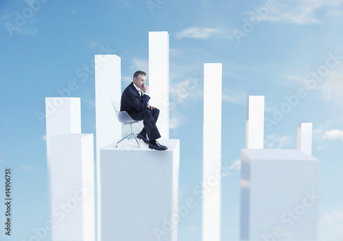 Business man sitting in chair on white pillar, digital composite