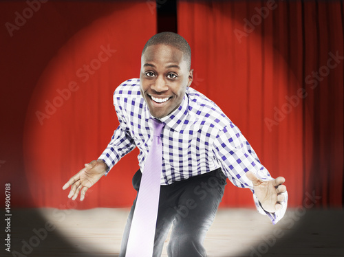 Businessman bending forward in front of red curtains, digital composite