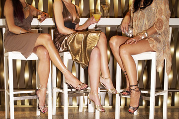 Stylishly dressed women sitting, legs crossed at bar, drinking, low section