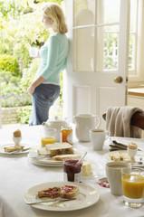 Woman With Tea standing in doorway, hand on hip, After Breakfast