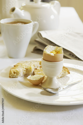 Half-Eaten Hard-Boiled Egg on dining room table, With Tea