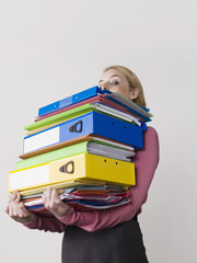 Female office worker carrying heavy binders, on white background