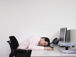 Male office worker asleep at desk in office