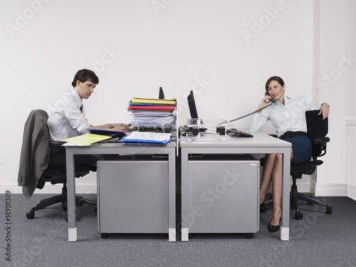 Hardworking man and relaxed woman in office
