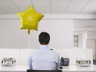 Man working alone beside balloon in office