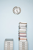 Office wall with clock, stack of paperwork in outbox on file cabinet