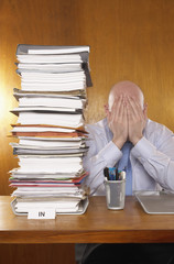 Businessman covering face with hands next to stack of paperwork at desk