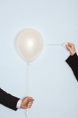 Businessmen holding and popping balloon, close-up of hands