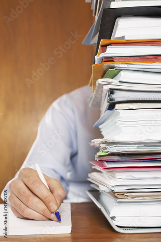 Man writing, close-up of arm and hand, sitting behind stack of paperwork at desk