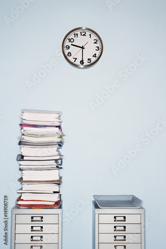 Office wall with clock, stack of paperwork in inbox on file cabinet