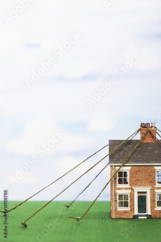 Model house tied down with string