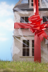Model house gift-wrapped with red ribbon and bow, close-up