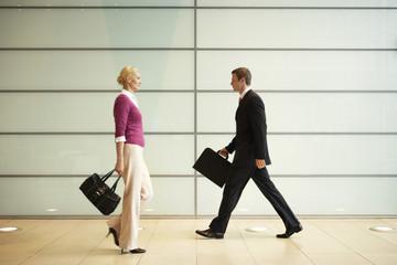 Businesspeople Walking  in Office Hallway, side view