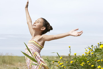 Pre-teen girl standing beside flowers, eyes closed, arms outstretched, side view