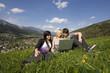 Junge Leute mit Laptop in Blumenwiese / Hintergrund Schladming