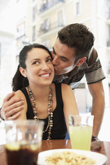 Young couple at sidewalk cafe, man kissing woman, portrait