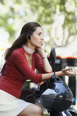 Businesswoman Using Cell Phone on Moped