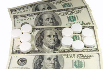 White pills forming 'one hundred' on a bunch of US dollars
