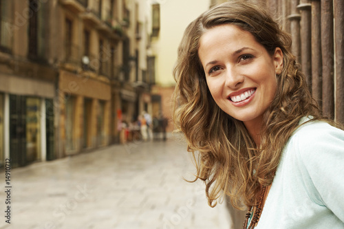 Young woman standing outside buildings in street, portrait.