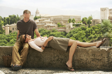 Tourist Couple Relaxing on Wall in Granada, Spain