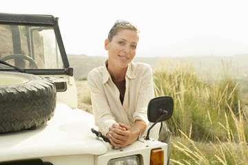Woman standing by four wheel drive car, outdoors, portrait
