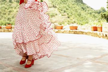 Woman flamenco dancing outdoors, close-up.