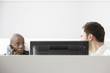 Two office workers sitting in office cubicle, one using phone