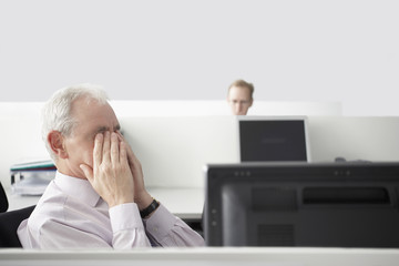 Mature businessman sitting, rubbing eyes in office cubicle