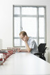 Office worker sitting using mobile phone at desk with document trays, side view