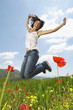 Woman jumping for joy in mountain meadow, portrait