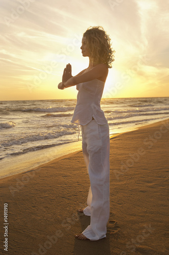 Young woman doing Tai Chi on beach, side view