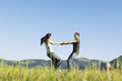 Young couple dancing in mountain field, side view, ground view